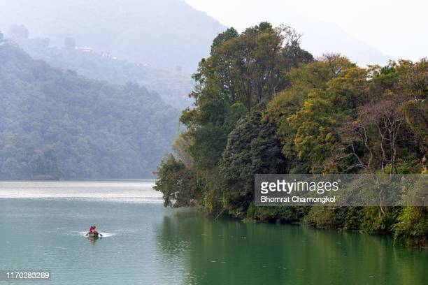 beautiful nature landscape of phewa lake with colourful wooden boats at pokhara, nepal - pokhara stock pictures, royalty-free photos & images