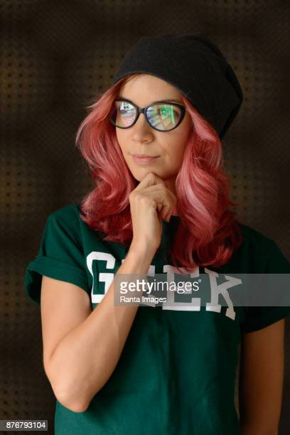 beautiful nerd woman with pink hair wearing geek shirt and eyeglasses - horn rimmed glasses stock pictures, royalty-free photos & images