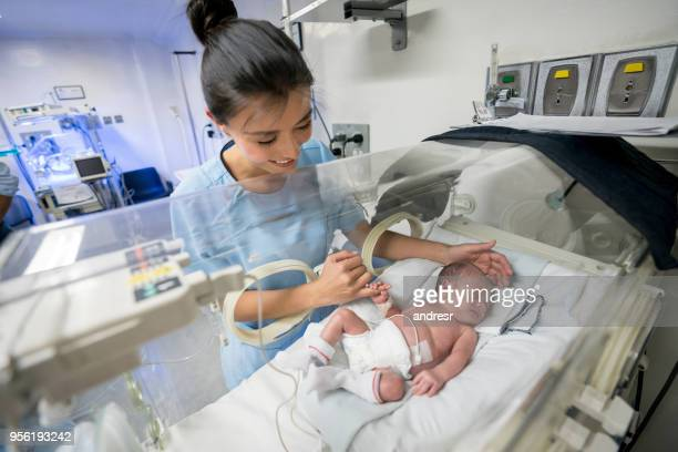 beautiful newborn baby in an incubator holding the nurses finger while she smiles - premature stock pictures, royalty-free photos & images