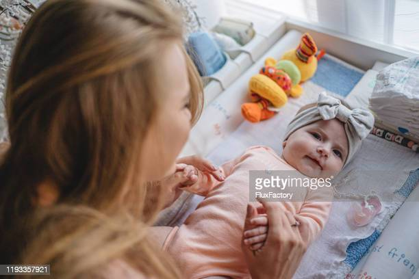 beautiful newborn baby with a ribbon headband and her young mother - baby changing mat stock pictures, royalty-free photos & images