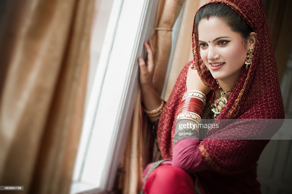 Beautiful newly married happy Indian young woman sitting near window. : Stock Photo