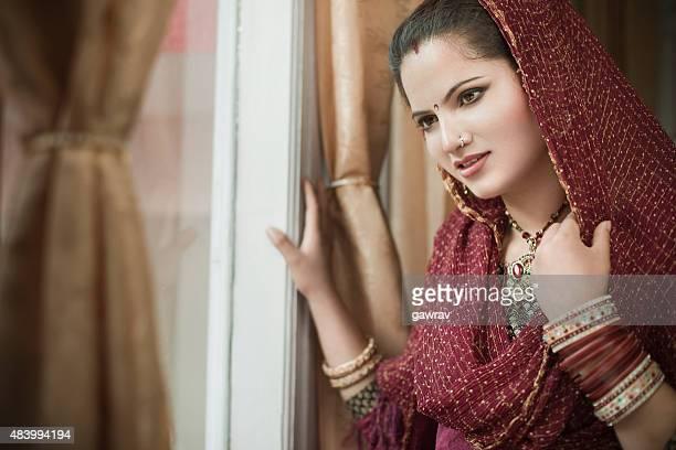 Notre magnifique mariée indienne heureuse jeune femme debout près de la fenêtre.