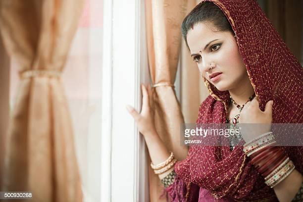 Beautiful newly married sad Indian young woman standing near window.