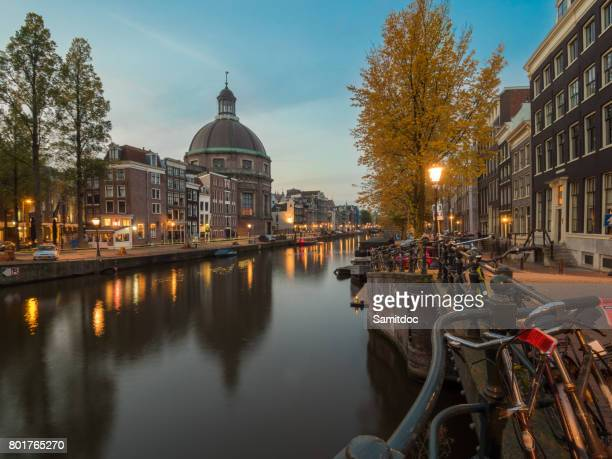 Beautiful night cityscape in Amsterdam, Netherlands. Reflected city lights in water with blue sky. Night illumination of buildings and boats near the water in the canal. Wonderful view on house