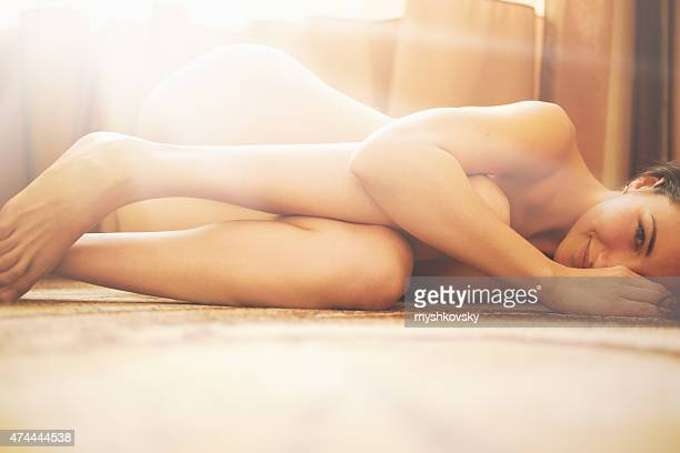 Beautiful nude woman lying on the floor.
