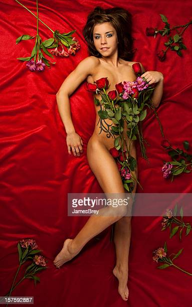 Beautiful Nude Young Woman on Red Velvet Bed With Roses