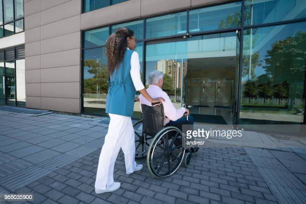 Beautiful nurse and senior patient on wheelchair going back to the nursing home after a stroll at the park