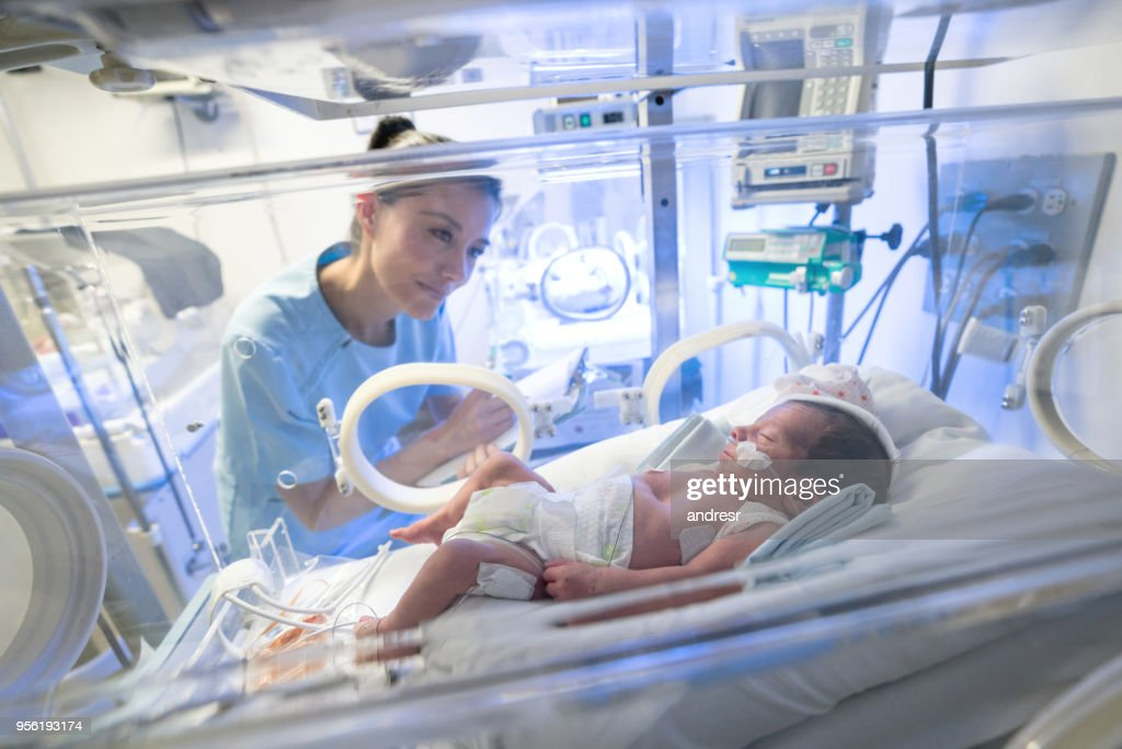 Beautiful Nurse Checking A Premature Baby In The Neonatal Intensive