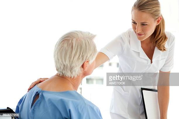 Beautiful nurse consoling senior patient