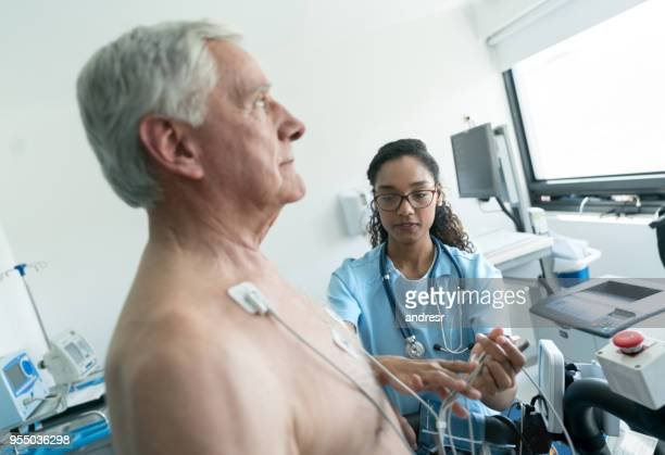 beautiful nurse getting ready a senior patient for a stress test on a treadmill - human heart stock pictures, royalty-free photos & images