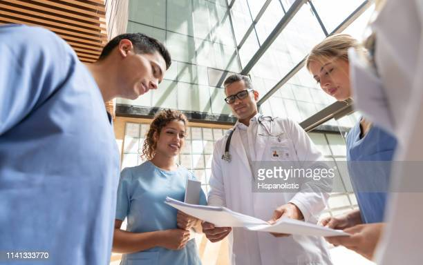 beautiful nurses and doctors discussing something while looking at paperwork - civilian stock pictures, royalty-free photos & images