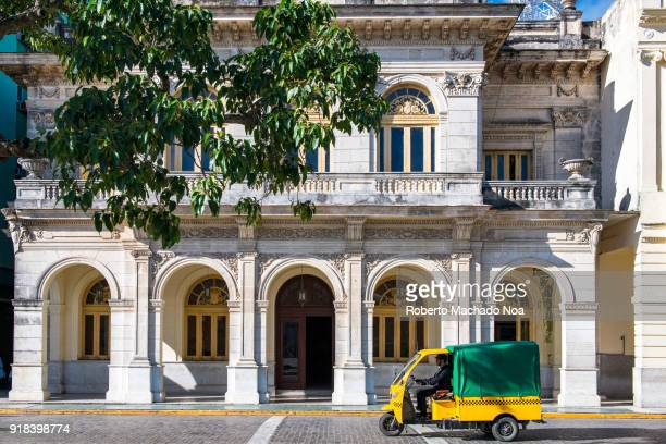 Beautiful old building facade in the Leoncio Vidal Park which is a Cuban National Monument area A newly introduced and governmentrun 'motoneta' for...