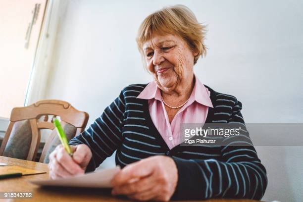 Beautiful old woman is smiling because she got a special letter