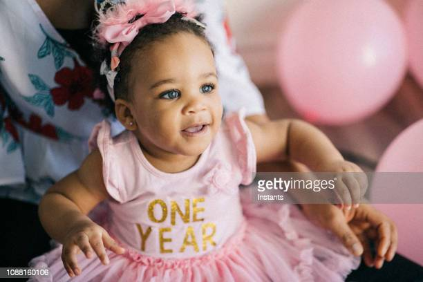 beautiful one year old baby girl, dressed in pink, celebrating her first birthday. - baby girls stock pictures, royalty-free photos & images