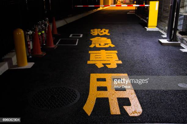 beautiful orange japanese letter in the asphalt of the tokyo city streets at night. - black alley stock photos and pictures