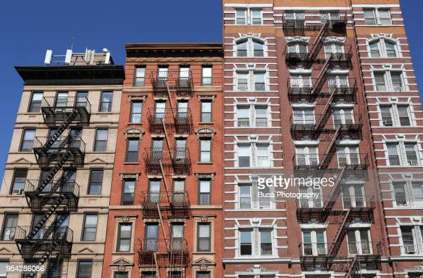 beautiful ornate facades of walkup buildings in the east village of manhattan, new york city. - east village stock pictures, royalty-free photos & images