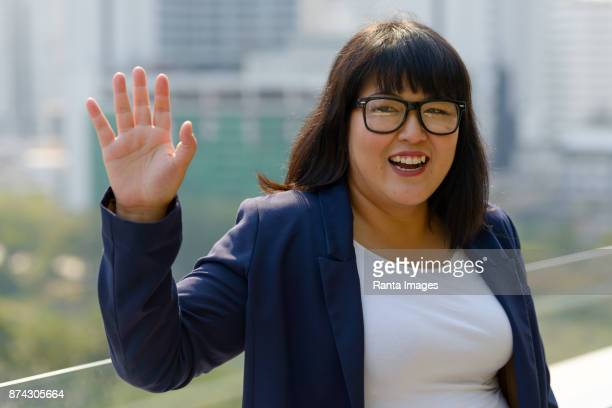 beautiful overweight asian businesswoman against view of the city in bangkok, thailand - chubby asian woman stock pictures, royalty-free photos & images