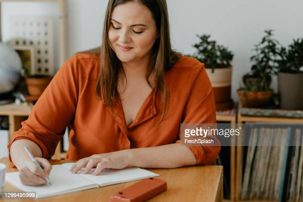 beautiful overweight woman sitting in her living room and writing a diary - list stock pictures, royalty-free photos & images