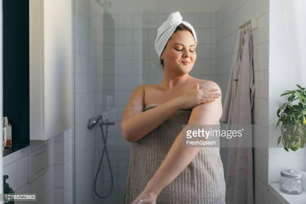 シャワーを浴びた後、ボディローションを塗るタオルに包まれた美しい太りすぎの女性 - タオル ストックフォトと画像