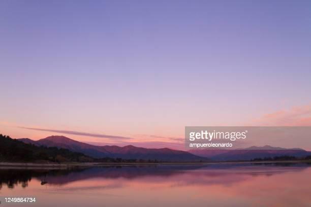 mooi het landschap patagonië van andes bergketen met hoge bergen met verlichte pieken, stenen in bergmeer, bezinning, violette hemel en mist bij de zonsondergang. - latijns amerika stockfoto's en -beelden