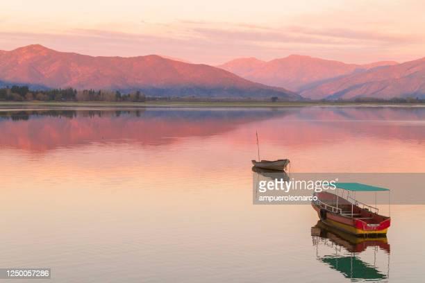 照らされた山、山の湖の石、反射、日没時の紫の赤紫の空と高い山との山の美しいパタゴニアの風景。 - リオネグロ州 ストックフォトと画像