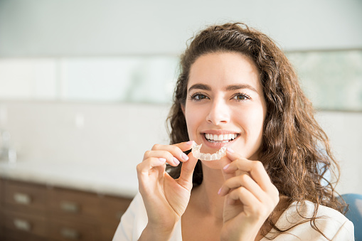 Beautiful Patient Holding Orthodontic Retainers In Dental Clinic 987925860