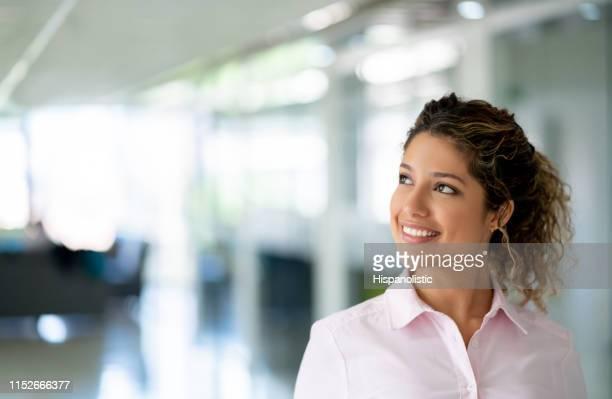 mulher nova pensativa bonita do negócio no escritório que olha afastado o sorriso - olhar para o outro lado - fotografias e filmes do acervo