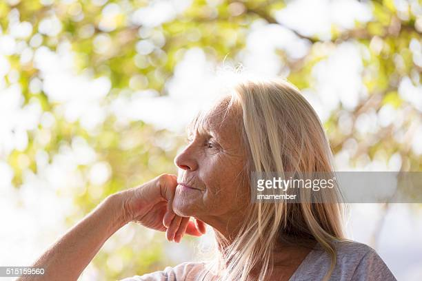 Beautiful pensive senior woman with hand on chin