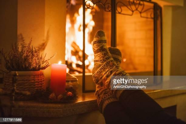 mooie foto van een voeten in de sokken die van kerstmis op de open haard verwarmen - opwarmen stockfoto's en -beelden