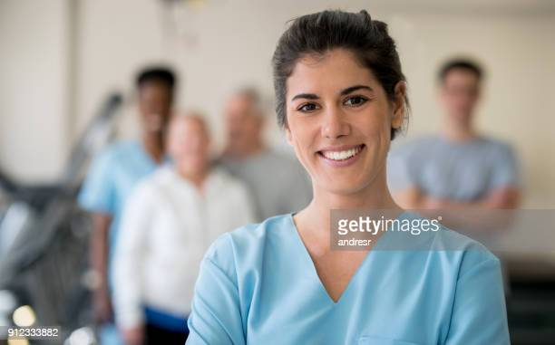 beautiful physical therapist at the clinic looking at camera smiling - group of doctors stock pictures, royalty-free photos & images