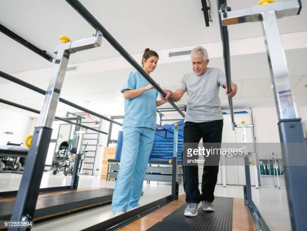 Beautiful physiotherapist helping a senior patient on his recovery walking between parallel bars