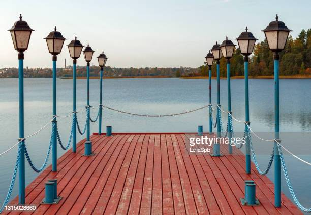 beautiful pier with lanterns on valdai lake on an autumn sunny day - bicolore photos et images de collection