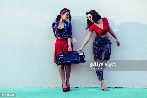 Beautiful pin-up girls leaning on the wall in the city street, carrying boom box