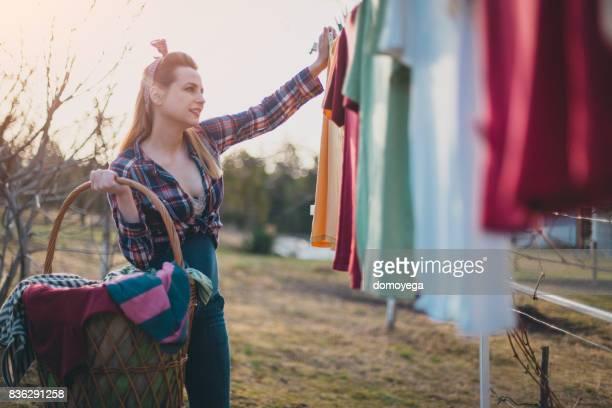 Beautiful pin-up woman carrying laundy basket outdoors