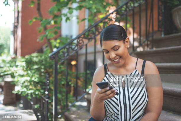 beautiful plus size dominican woman in usa using phone for communication. - dominican ethnicity stock photos and pictures