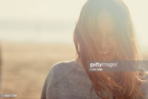 a beautiful portrait of a woman at the beach in the summer with warm sunlight glow. - glowing stock pictures, royalty-free photos & images