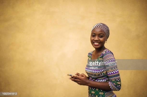 beautiful portrait of a young african girl on her mobile phone girl power - tanzania stock pictures, royalty-free photos & images