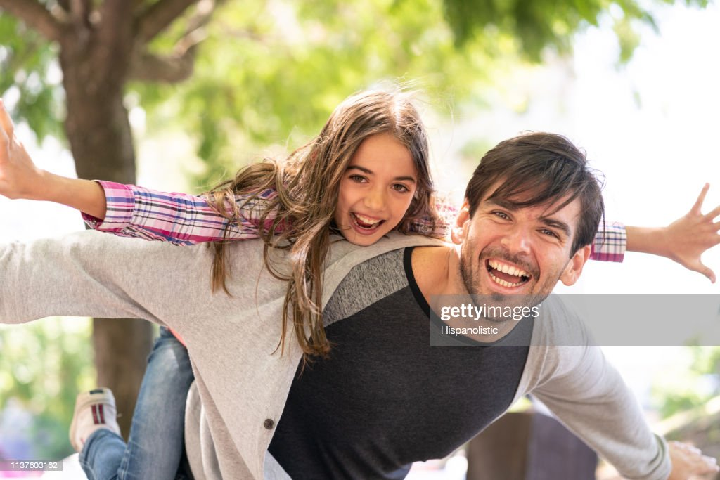 Beautiful portrait of dad carrying daughter on back playing like an airplane while both laughing at camera : Stock Photo