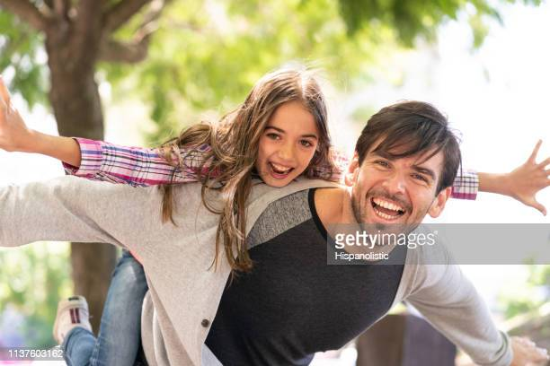 Beautiful portrait of dad carrying daughter on back playing like an airplane while both laughing at camera