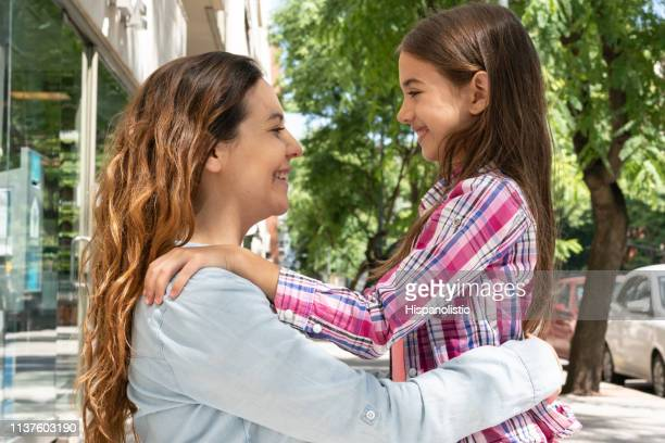 beautiful portrait of mother and daughter hugging while looking at each other smiling - hispanolistic stock photos and pictures