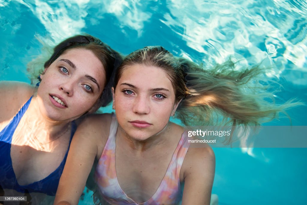 Beautiful portrait of two cousins in pool water. : Stock Photo