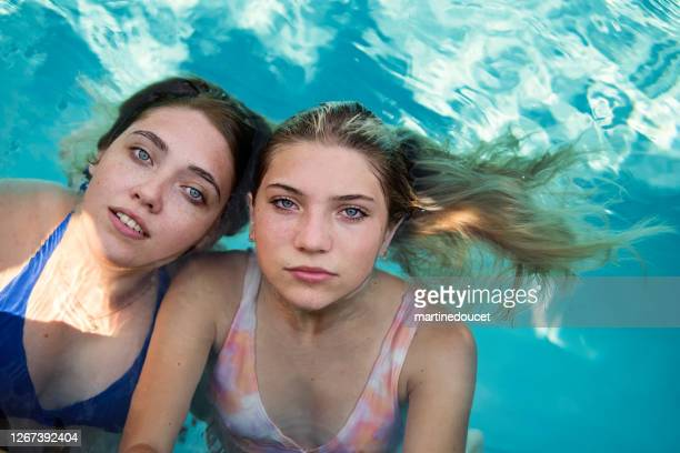 """beautiful portrait of two cousins in pool water. - """"martine doucet"""" or martinedoucet stock pictures, royalty-free photos & images"""