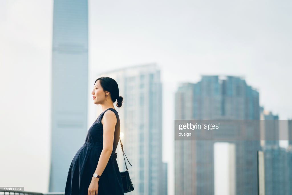 Beautiful pregnant Asian woman standing against modern cityscape enjoying view : Stock Photo