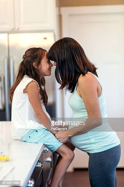 Beautiful pregnant mother and daughter touch foreheads together