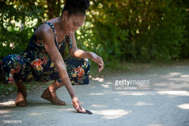 Beautiful pregnant woman approaching a toad in the park