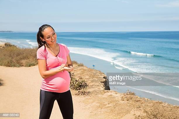 Beautiful pregnant woman checking her heart rate after run