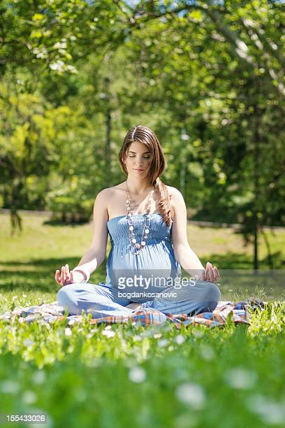 Beautiful pregnant woman meditating in the park