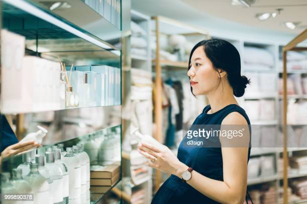 beautiful pregnant woman shopping for beauty products in shopping mall - cosmetics stock pictures, royalty-free photos & images
