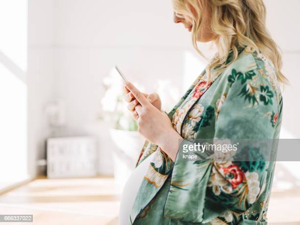 Beautiful pregnant woman with smart phone in the kitchen
