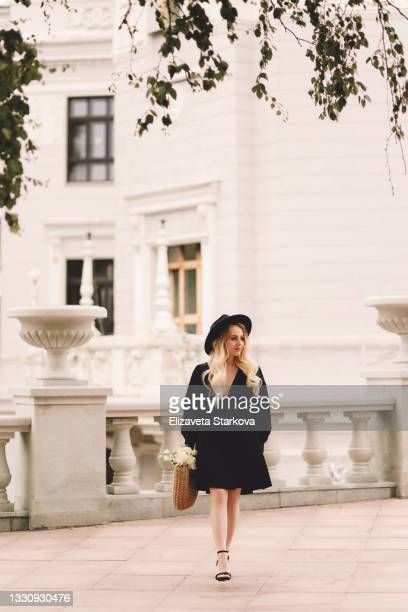 a beautiful pretty cute young woman with blonde curls and makeup in a hat and an elegant black dress holds a wicker bag with flowers and bread baguettes walks in a well-groomed park among plants and trees near the theater and buildings in the city - dress stock pictures, royalty-free photos & images